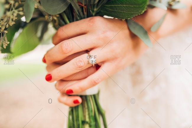 Close up of the bride's engagement ring while she holds her bouquet