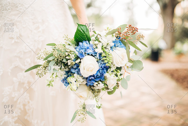 Bride holding a blue and white bouquet