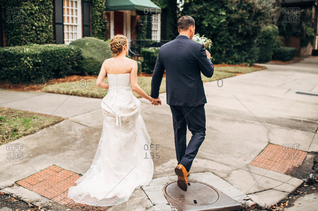Rear view of bride and groom holding hands walking on sidewalk after eloping