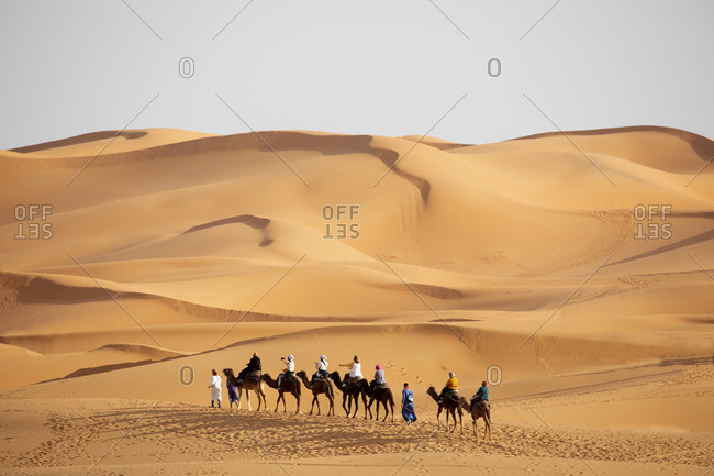 Erg Chebbi great sand dunes of western Sahara region with tourists having a camel ride at sunset, Merzouga, Morocco