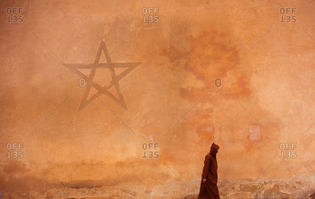 Marrakesh, Morocco - April 5, 2019: Man in traditional djellaba clothing walking by huge wall with Moroccan star painted