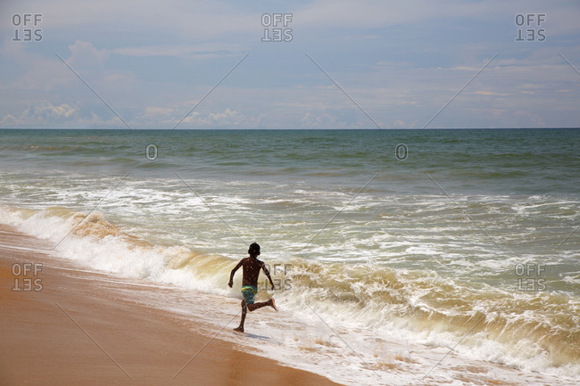 Local boy playing in surf on a beach in Colombo City, Sri Lanka