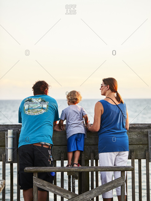 Charleston, South Carolina, USA - September 7, 2018: Rear view of family looking out at the ocean from a boardwalk