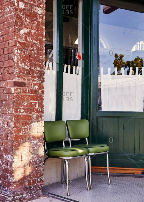 Charleston, South Carolina, USA - September 7, 2018: Green chairs outside of a green and brick building