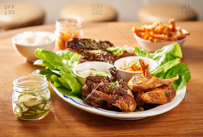 Barbeque chicken wings at a Korean BBQ restaurant with kimchi and pickles