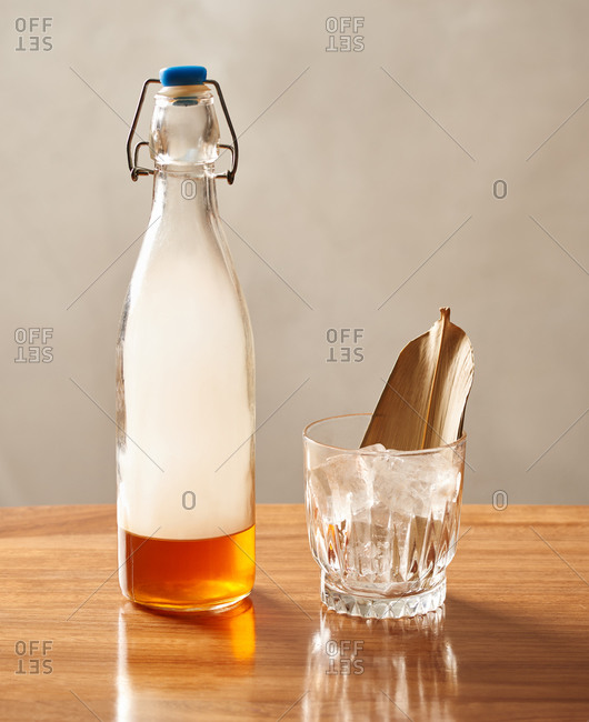 A maple smoked whiskey cocktail ready to be poured into a glass with ice cubes