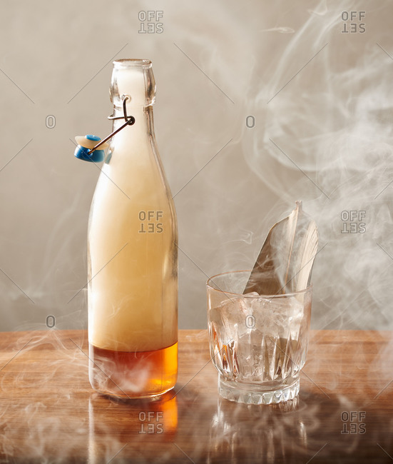 Smoke escaping from a maple smoked whiskey cocktail, ready to be poured into a whiskey glass