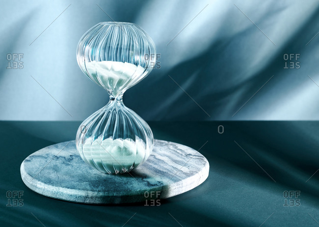 A decorative glass hourglass sand timer against a shadowy blue background