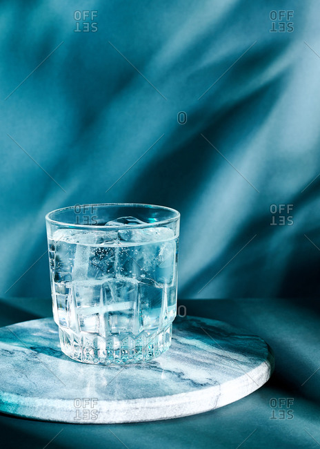 A glass of gin with ice against a teal shadowy background