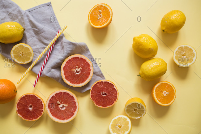 Sliced citrus fruits on yellow background with blue towel and straws