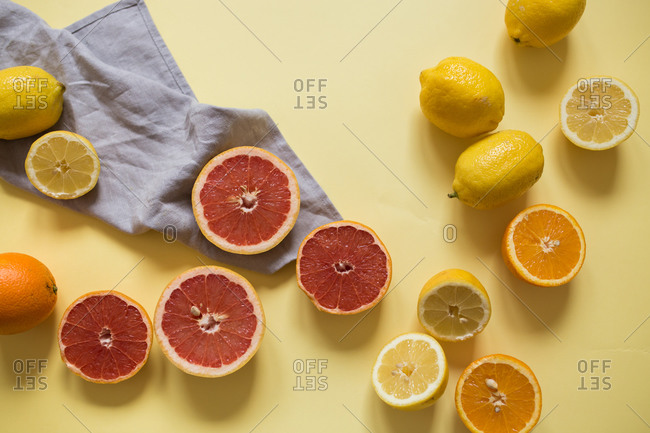 Sliced citrus fruits on yellow background with blue towel