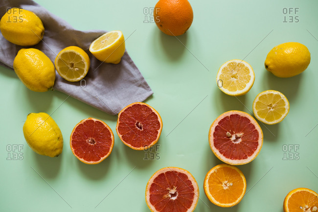 Overhead view of sliced citrus fruits on light green background with blue towel