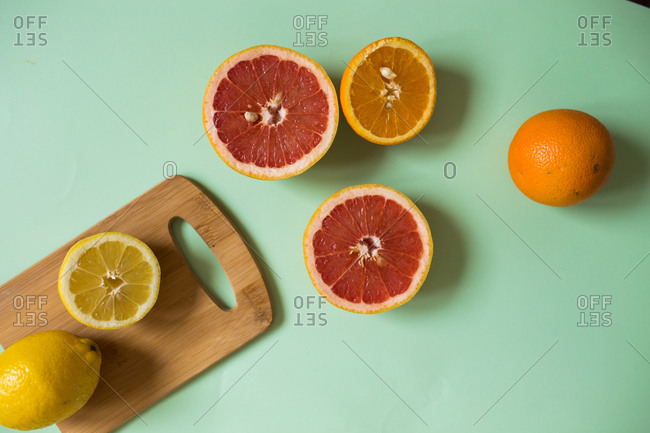 Overhead view of sliced citrus fruits on light green background with cutting board