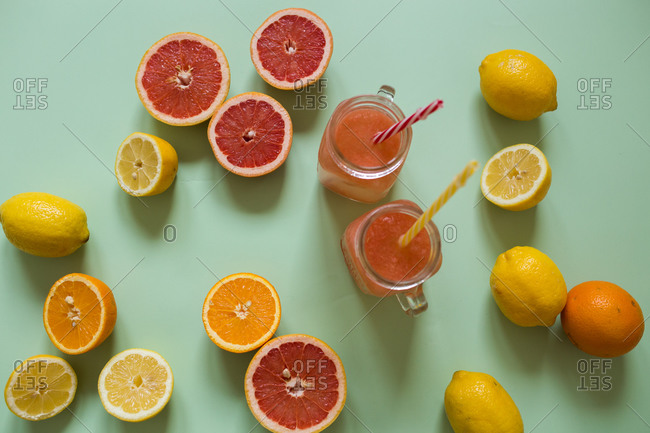 Two glasses of fresh juice with sliced citrus on light green background