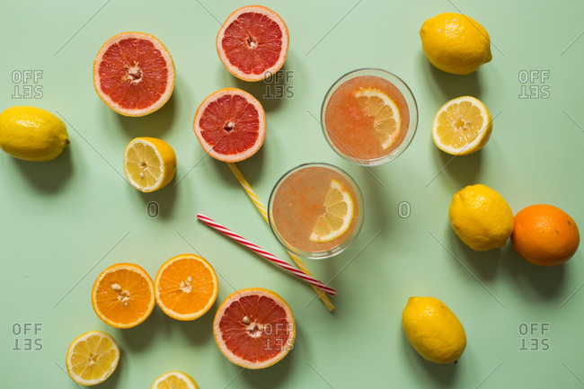 Two glasses of fresh citrus juice with sliced citrus on light green background