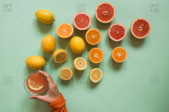 Woman holding glass with fresh citrus juice