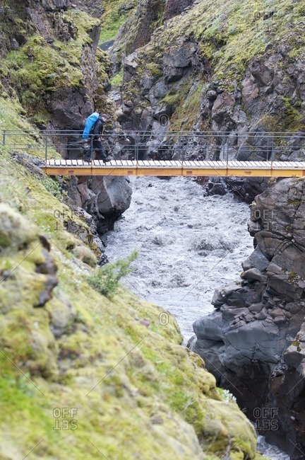 August 4, 2011: Hiker crosses a bridge on the way from Skogar to Landmannalaugar, Iceland, Europe