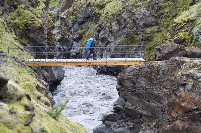 Hiker crosses a bridge on the way from Skogar to Landmannalaugar, Iceland, Europe