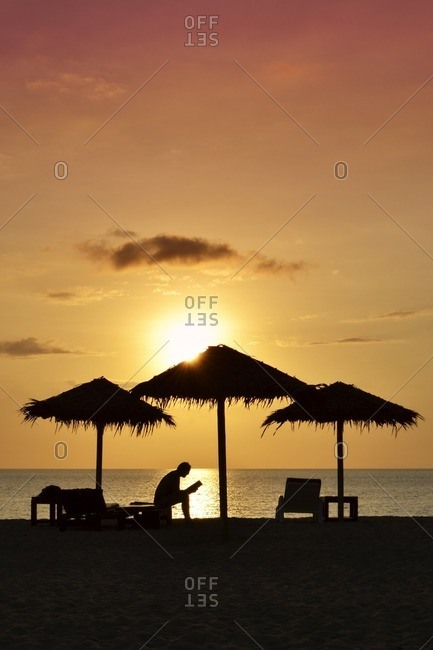 Person reading book on the beach at sunset, silhouette, Kib Hotel, Koh Kho Khao Island, Southern Thailand, Southeast Asia