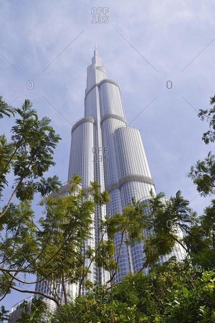 February 15, 2012: Burj Khalifa in front of blue sky, exotic flowers, architecture, Dubai Business Bay, Emirate of Dubai, United Arab Emirates, Arabian Peninsula, Middle East