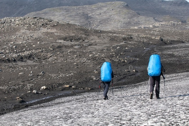 Hikers cross a snow field on the way from Skogar to Landmannalaugar, Iceland, Europe
