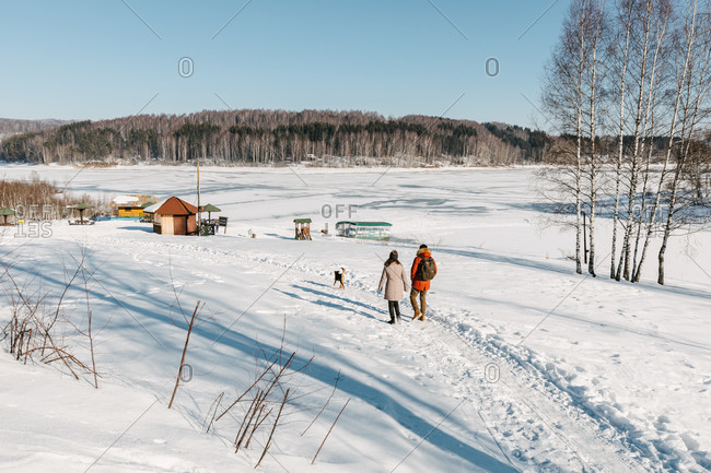 Two friends and a dog walking down the snow path to the wonderful frozen lake