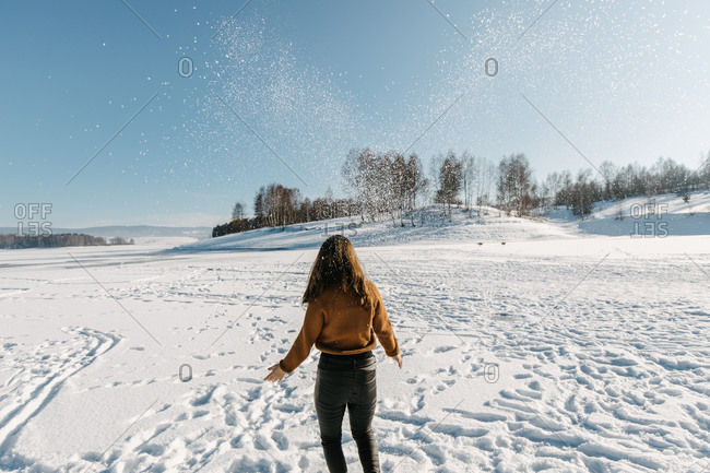 Young woman throwing snow in the air, against the beautiful frozen lake covered with snow
