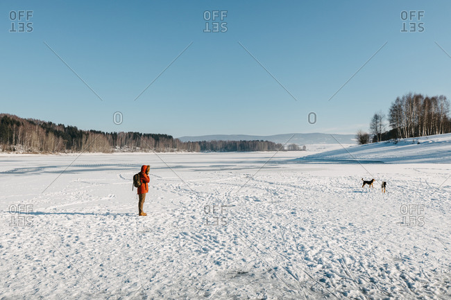 Young adventurous man with a backpack standing on the frozen lake