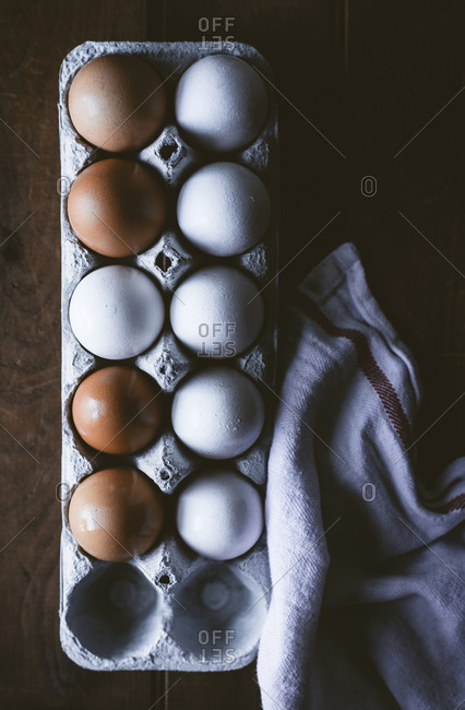 Eggs in a crate on a wooden surface.