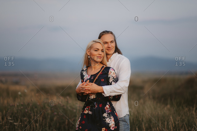 Happy couple embraced in a field