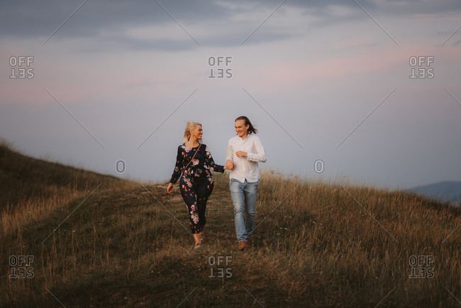 Smiling couple walking hand in hand in a field