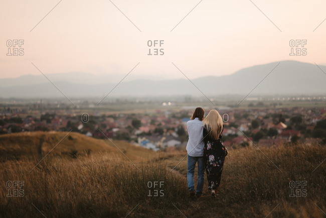Rear view of couple overlooking city from hilltop at sunset