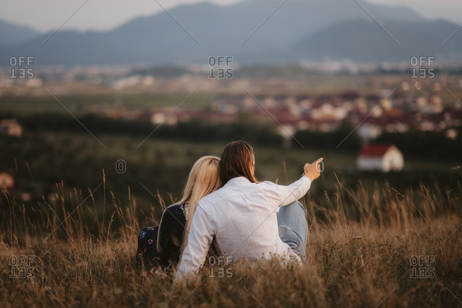 Rear view of couple sitting on hilltop pointing while overlooking city at sunset