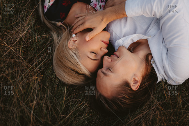 Overhead view of a man preparing to kiss woman while lying in a field together