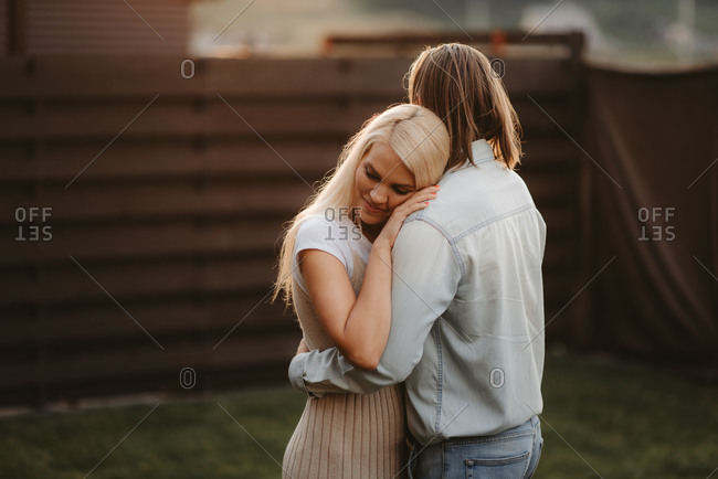 Man embracing blonde woman in a backyard