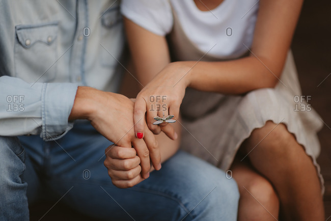 Close up of an engaged couple's hands and dragonfly ring