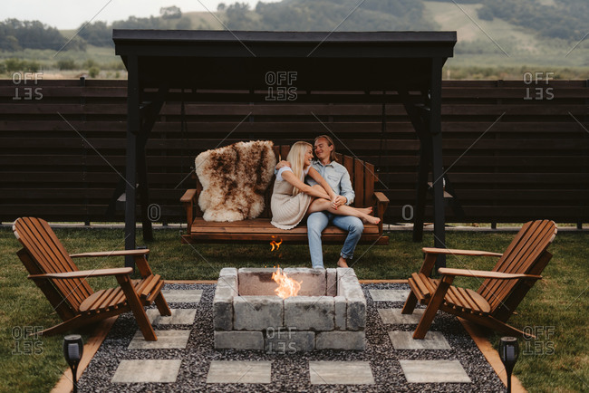 Couple relaxing on a wooden swing by a fire