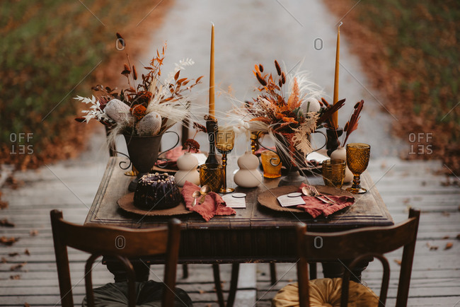 Rustic table set with fall decorations and dessert outdoors