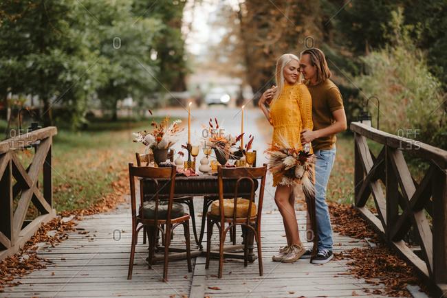 Couple standing on bridge beside rustic table