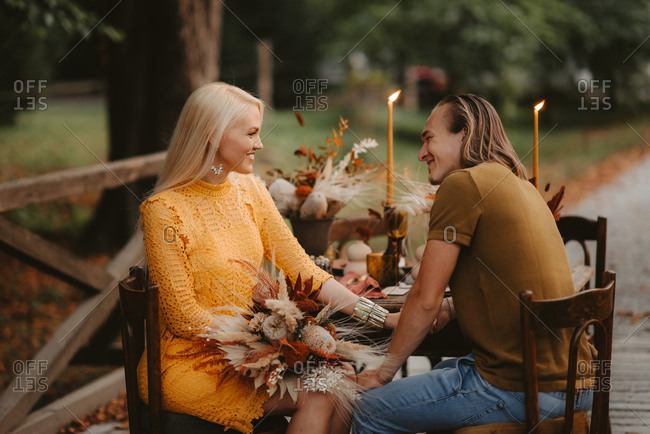 Couple sitting at rustic table during their autumn wedding