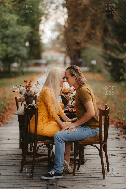 Couple sitting at rustic table preparing to kiss during their autumn wedding