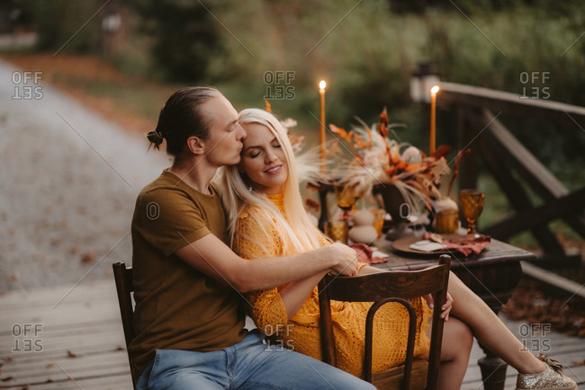 Couple sitting embraced at rustic table during their autumn wedding