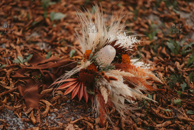 Autumnal bridal bouquet on the ground covered in leaves