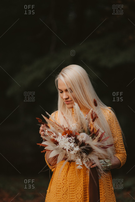 Beautiful blonde bride holding fall wedding bouquet