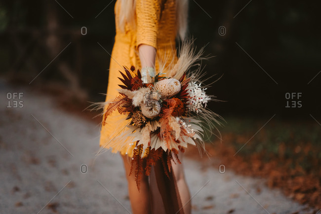 Bride wearing a yellow dress and holding fall wedding bouquet