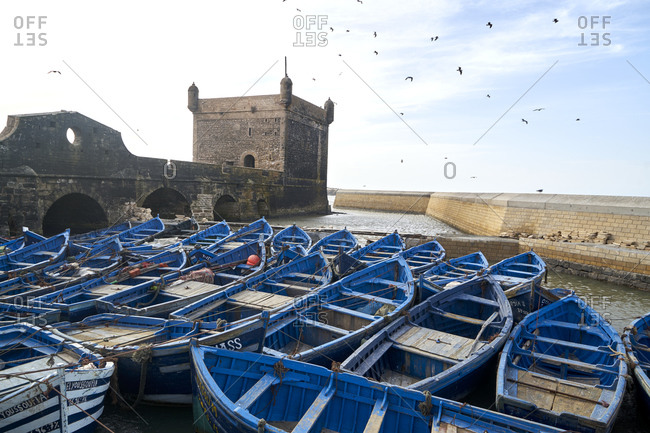 November 8, 2017: The Port of Essaouira, Essaouira, Morocco; November 8 2017; Blue fishing boats in Essaouira Port, formerly Mogador, Morocco, North Africa, Africa. The Port of Essaouira is not only home to many fishing boats and vessels, it is a popular tourist attraction and has a significant and interesting history attached to it. Fishing is done for local distribution and plays a significant role in the atmosphere and lure to the port.