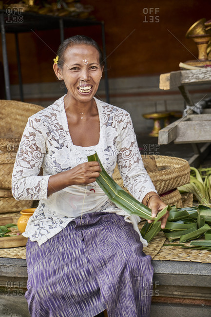 February 19, 2017: Ubud, Bali, Indonesia; February 19, 2017: Balinese woman making worship baskets at palace in Ubud. The Ubud Palace, officially Puri Saren Agung, is a historical building complex situated in Ubud, Gianyar Regency of Bali, Indonesia.