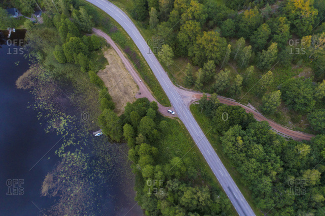 Aerial of a road by a lake and forest before sunset in summer
