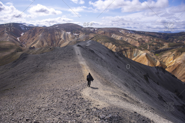 Man with cape walking down trail on top of mountain in Iceland