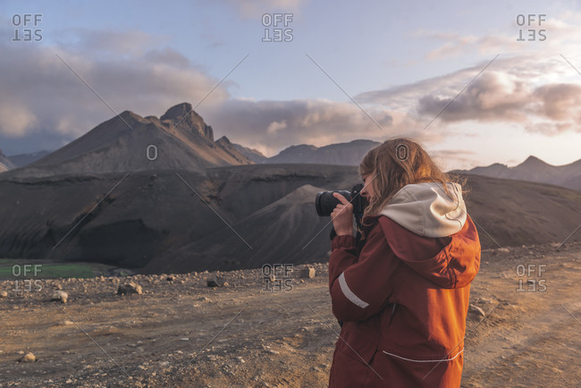 Young woman taking photographs of mountains in highlands of Iceland